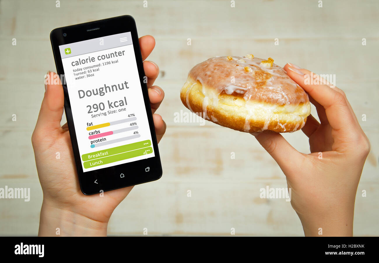 Calorie counter concept - young woman holding mobile phone with calorie counter app on the screen. - Stock Image