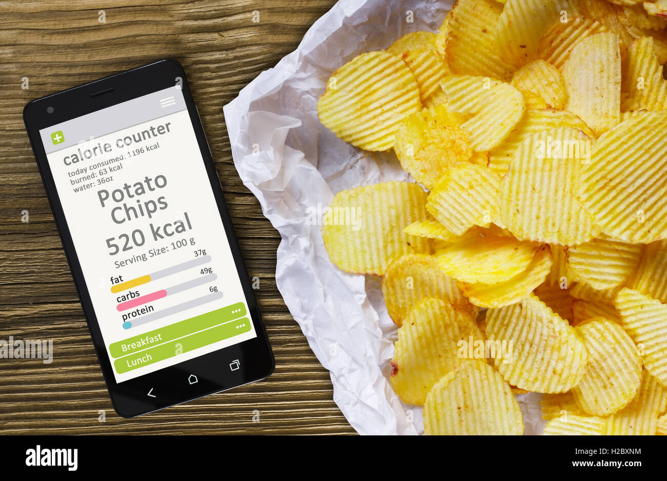Calorie counter concept concept - mobile phone with calorie counter app on the screen and potato chips. Wooden table - Stock Image