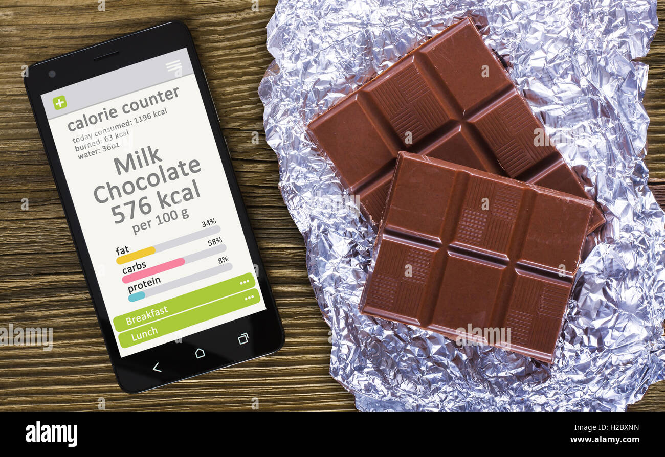 Calorie counter concept  concept - mobile phone with calorie counter app on the screen and milk chocolate. Wooden - Stock Image