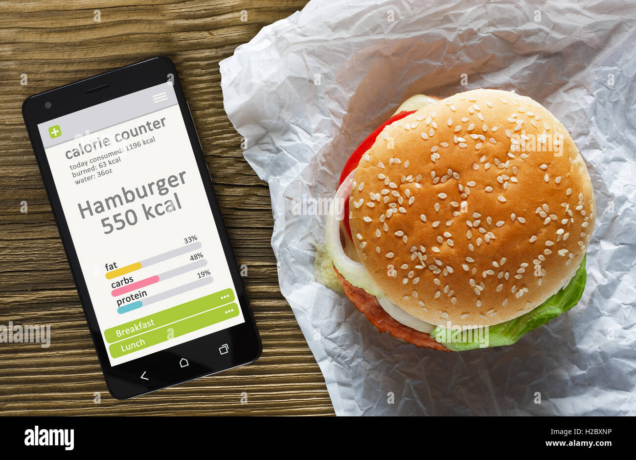 Calorie counter concept - mobile phone with calorie counter app on the screen and hamburger. Wooden table as background - Stock Image