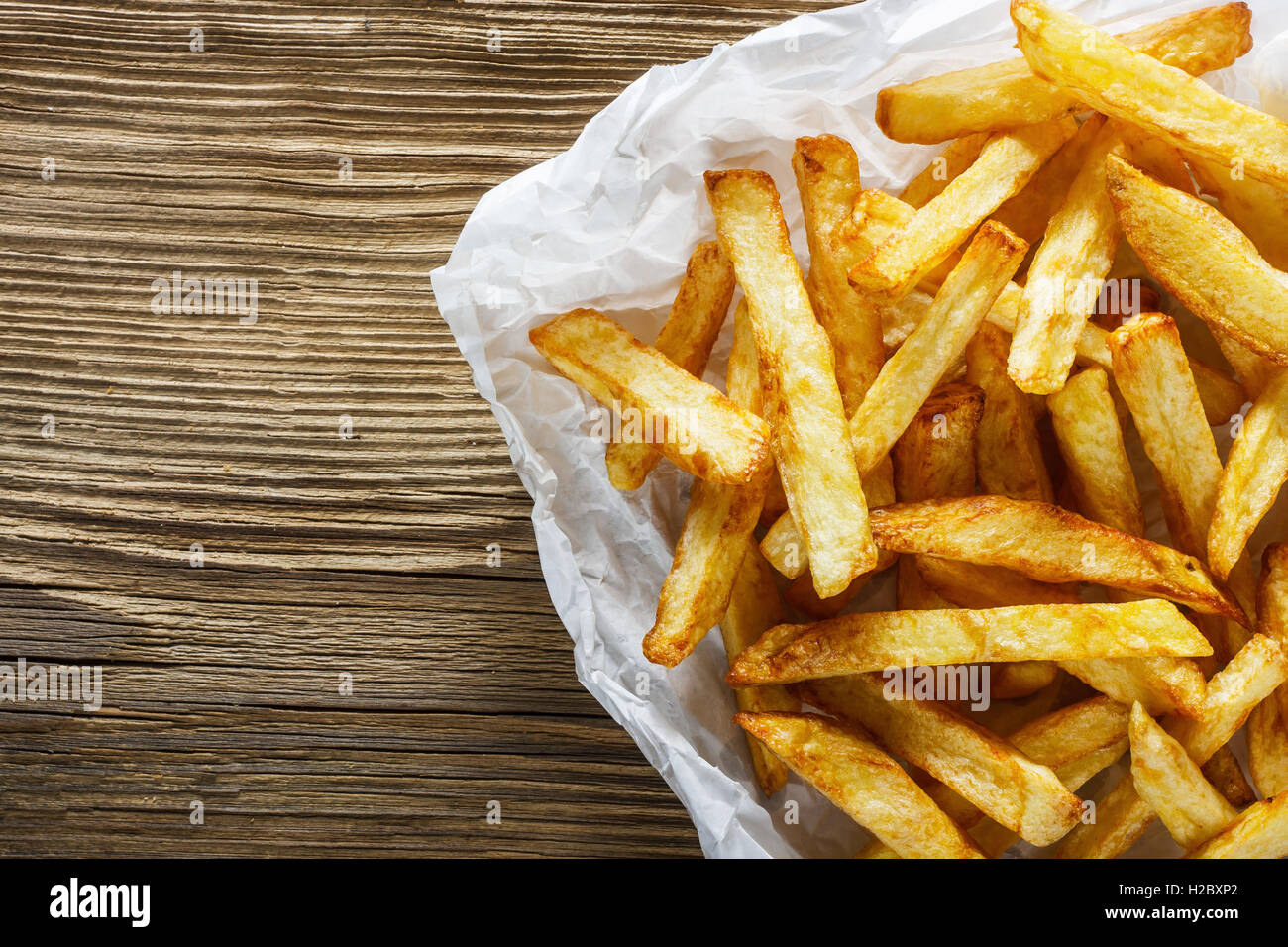 French fries on wooden table - Stock Image