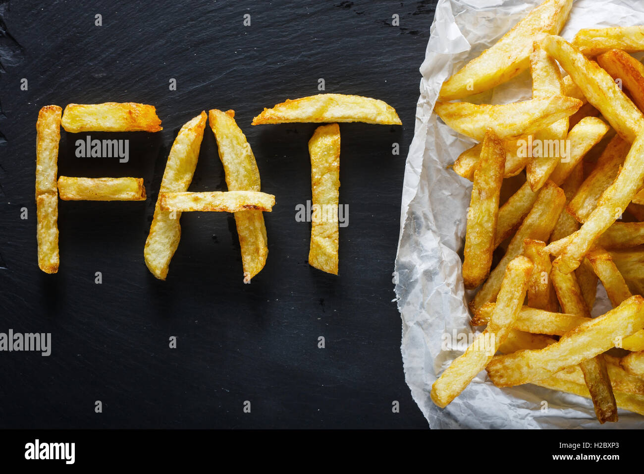 Unhealthy food concept - french fries on slate board - Stock Image