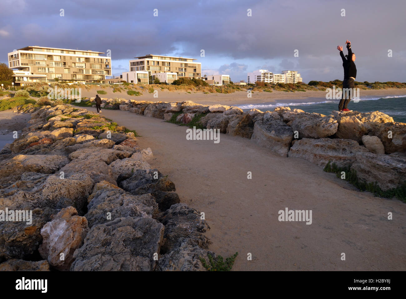 Person enjoying stormy evening seas, South Beach, South Fremantle, Perth, Western Australia. No MR or PR - Stock Image