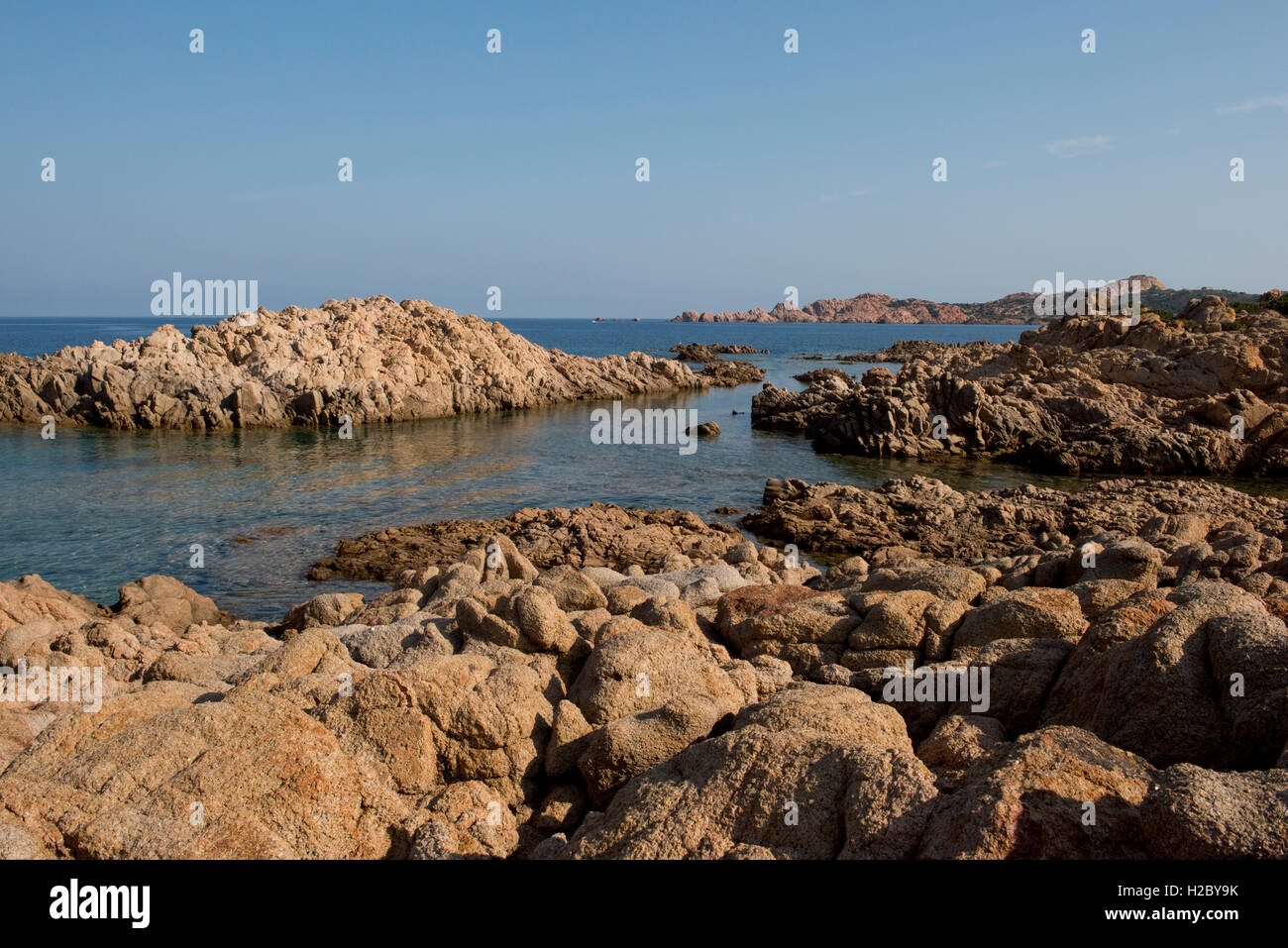 Red granite rugged coastline and blue sea of the Isola Rossa in western Sardinia, September - Stock Image