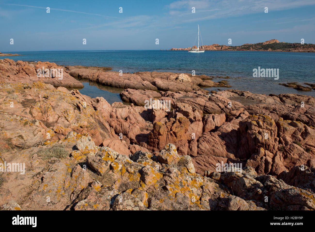 Red granite rugged coastline and blue sea and moored yacht off the Isola Rossa in western Sardinia, September - Stock Image