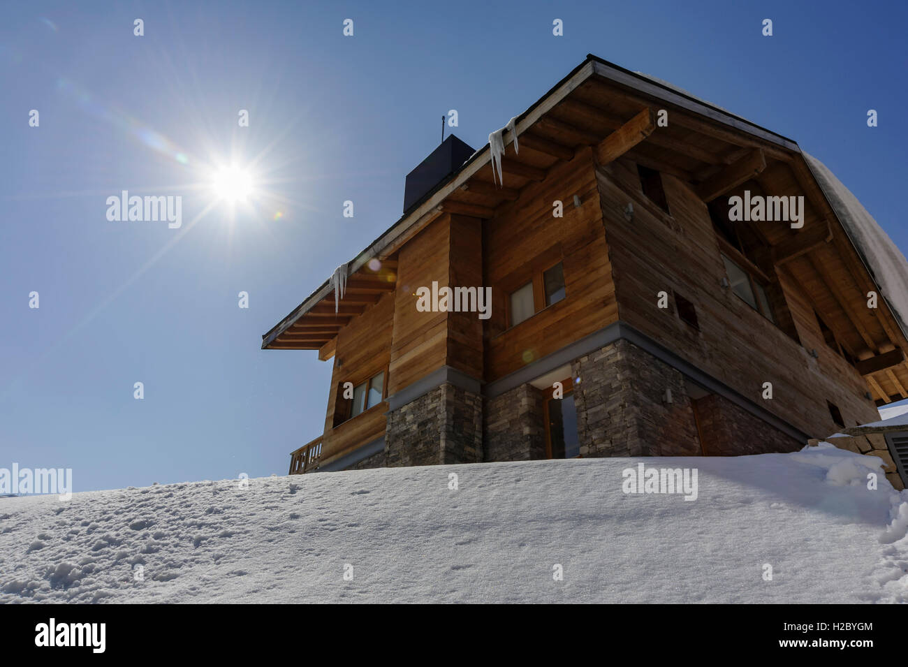A chalet in wood and stone during winter in Mzaar Kfardebian ski resort in Lebanon (contre-jour) - Stock Image
