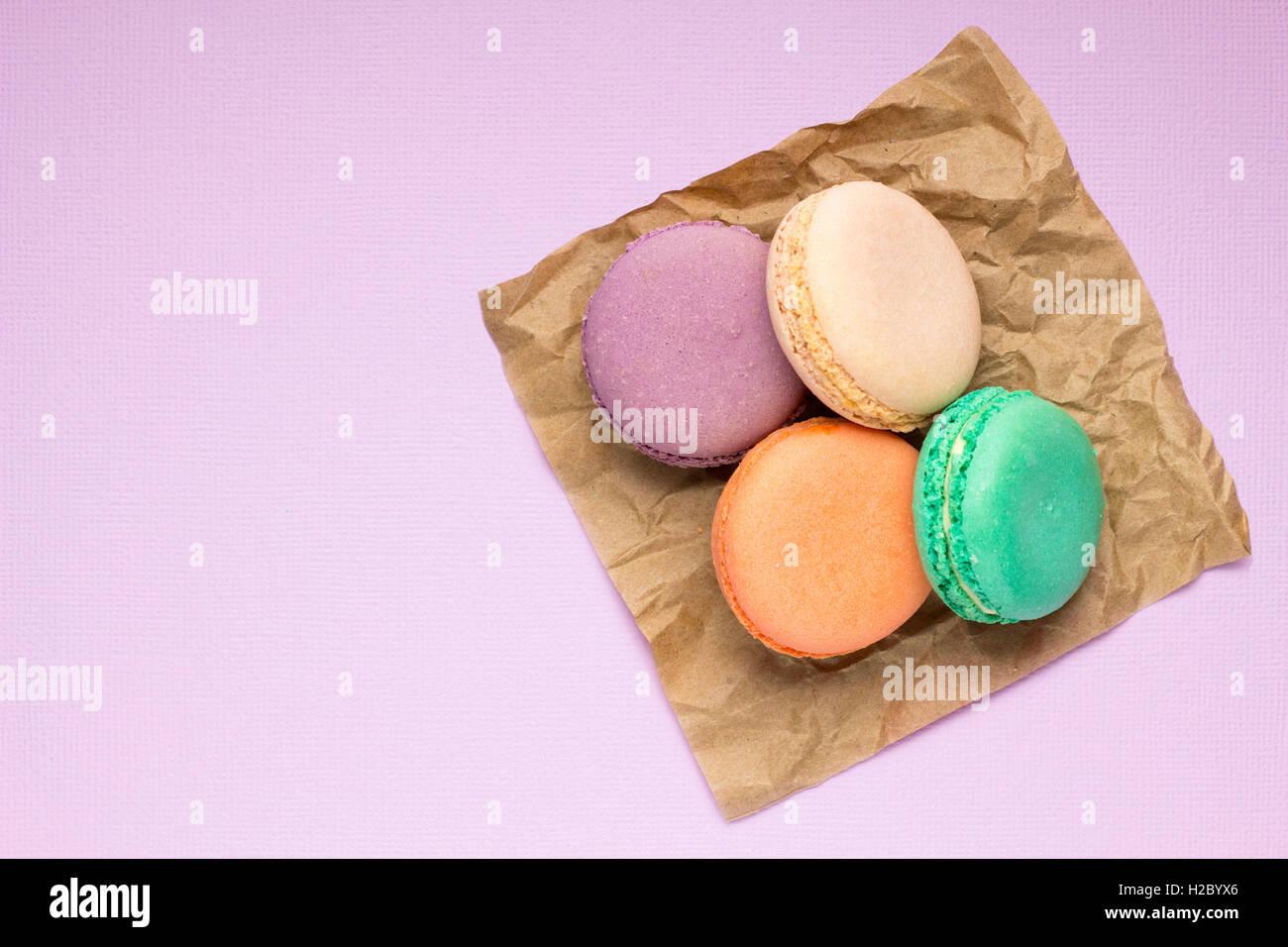 Creative photo of macaroons on purple background. - Stock Image