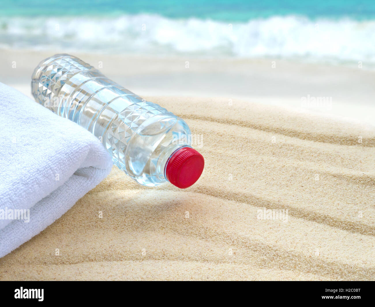 Mineral water bottle and towel on the beach - Stock Image