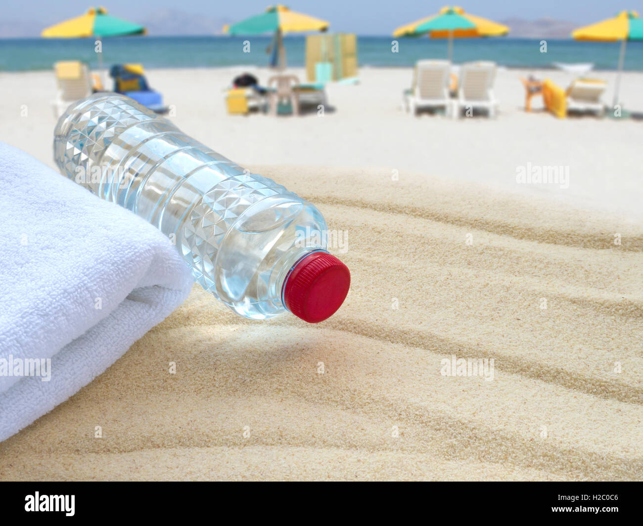 Mineral water bottle and towel on the public beach - Stock Image