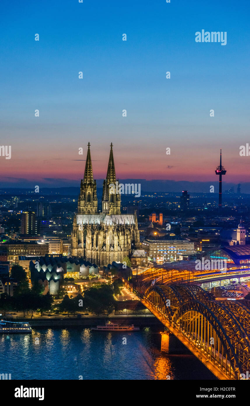 River Rhine at dusk, looking towards Cologne Cathedral with the Hohenzollern Bridge in the foreground, Cologne, - Stock Image