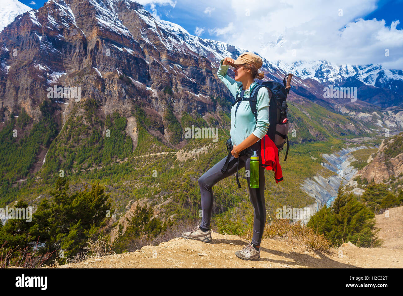 Beautiful Woman Traveler Backpacker Mountains Path.Young Girl Looking Right Way and Take Rest.North Summer SnowStock Photo