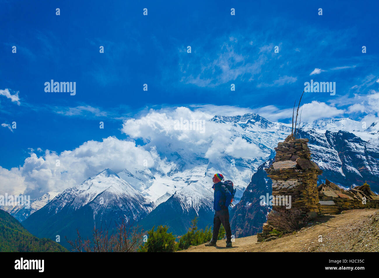 Photo Man Traveler Backpacker Mountains Way.Young Guy Looking Away Take Rest Sunny Terrace Path.Snow Landscape Background. Stock Photo