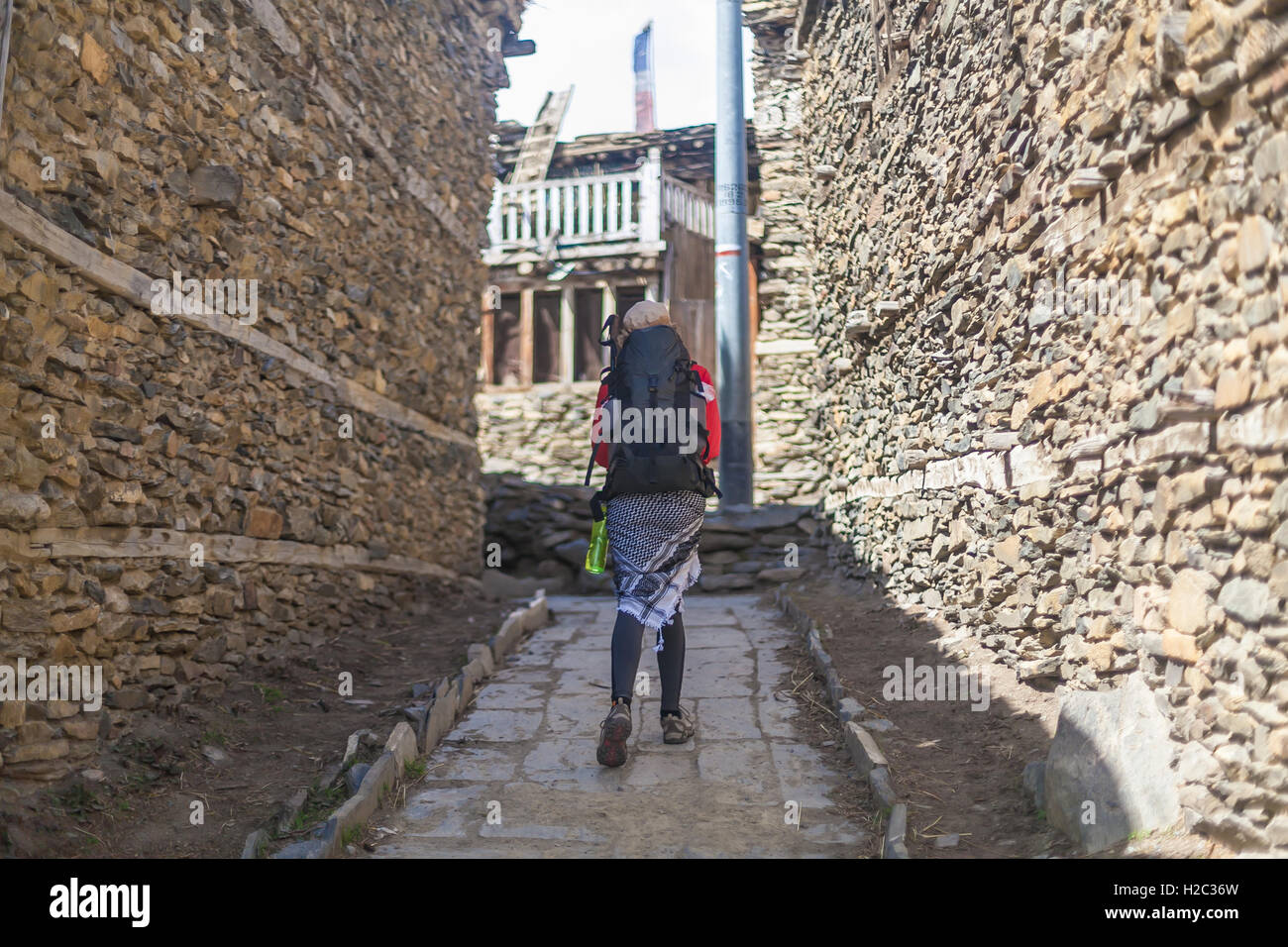 Young Pretty Woman Wearing Red Jacket Backpack Crossing Mountains Village.Mountain Trekking Rocks Path.Old Town Stock Photo