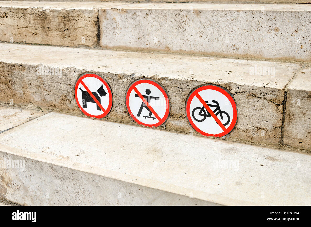 Sign prohibits dogs pass, travel on a bike and skateboard. Close-up. - Stock Image