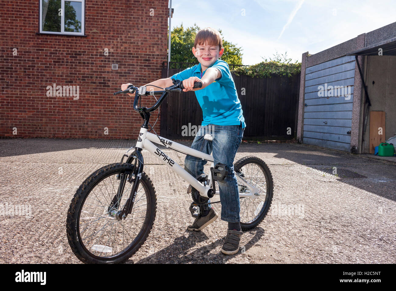 A young boy sat on a BMX bicycle outside on a sunny day wearing a bright blue Beaver Scout uniform shirt - Stock Image