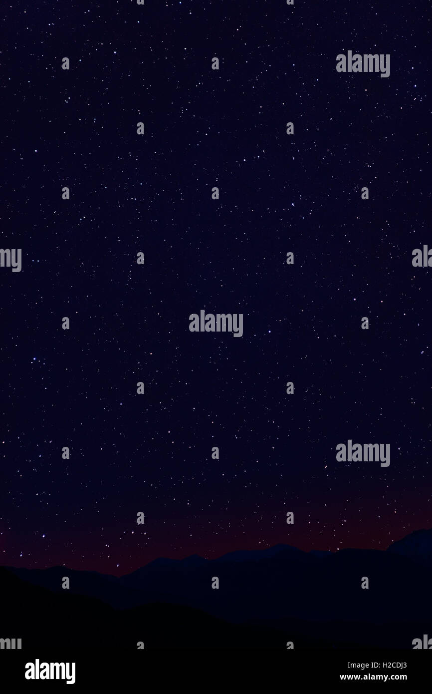 Astronomy photo with dark night sky covered by stars with mountain landscape at the horizon as a background - Stock Image