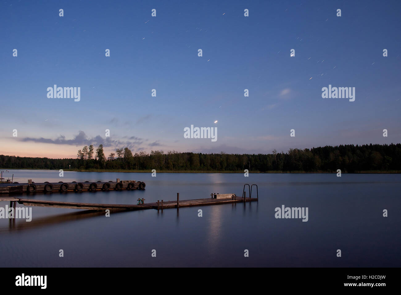 Nightscape (landscape) with sunrise, stars that are reflected in the water surface (star trails are visible) - Stock Image