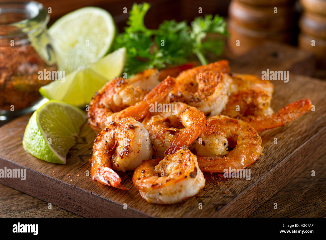 Delicious sauteed shrimp with cajun seasoning and lime on a maple plank. - Stock Image