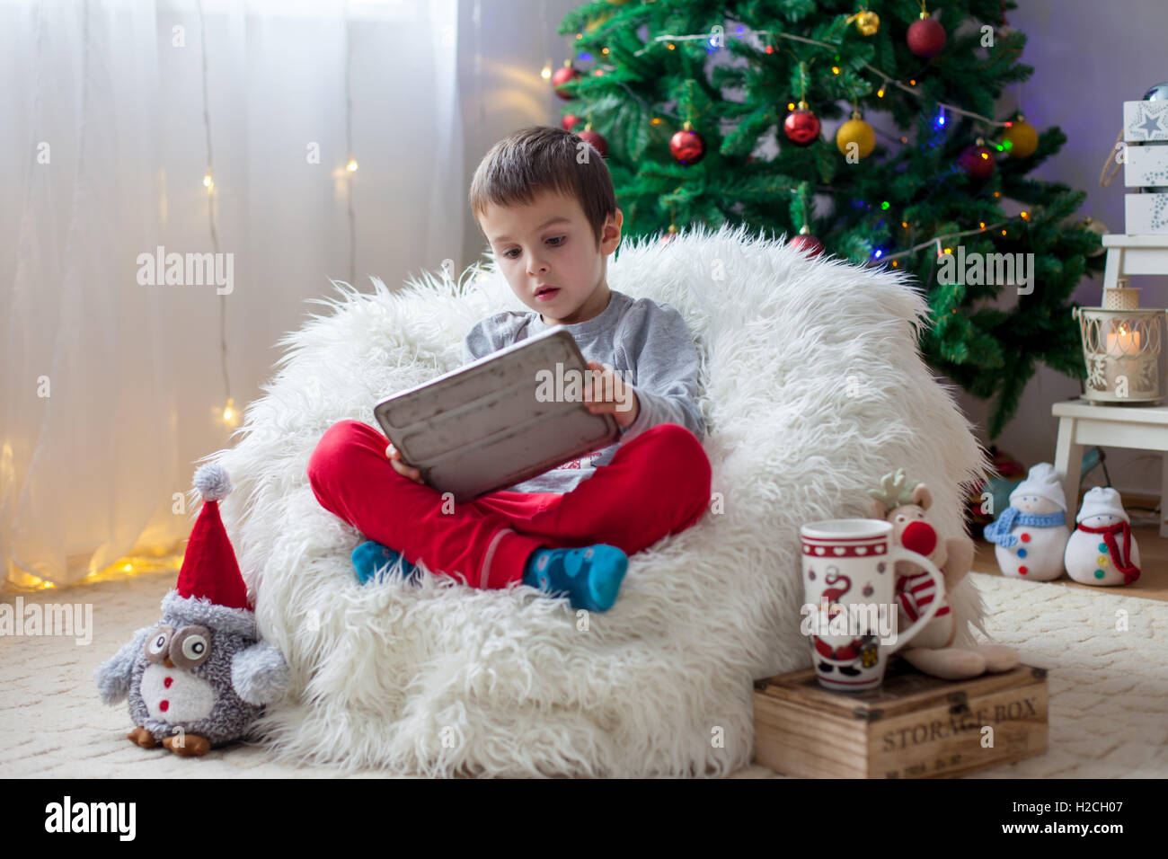 Cute little sick boy, sitting on bean bag, playing on tablet at home - Stock Image
