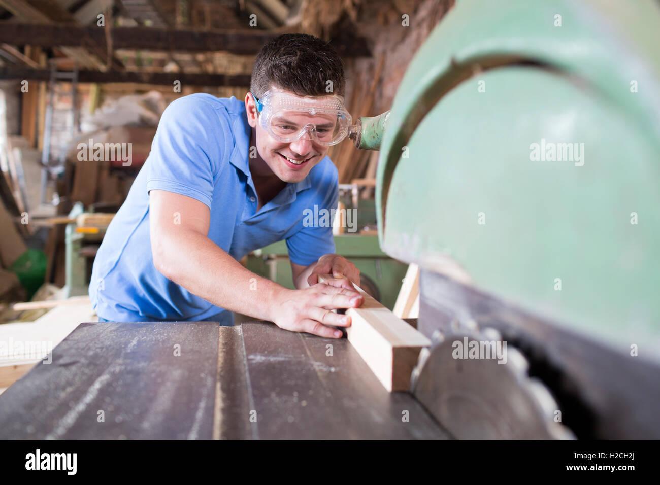 Carpenter Cutting Wood On Circular Saw - Stock Image