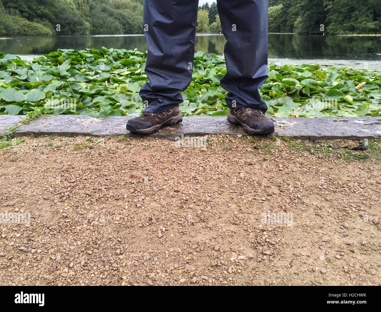 Man's legs wearing waterproof trousers and walking boots. At Newstead Abbey, Newstead, Notting - Stock Image