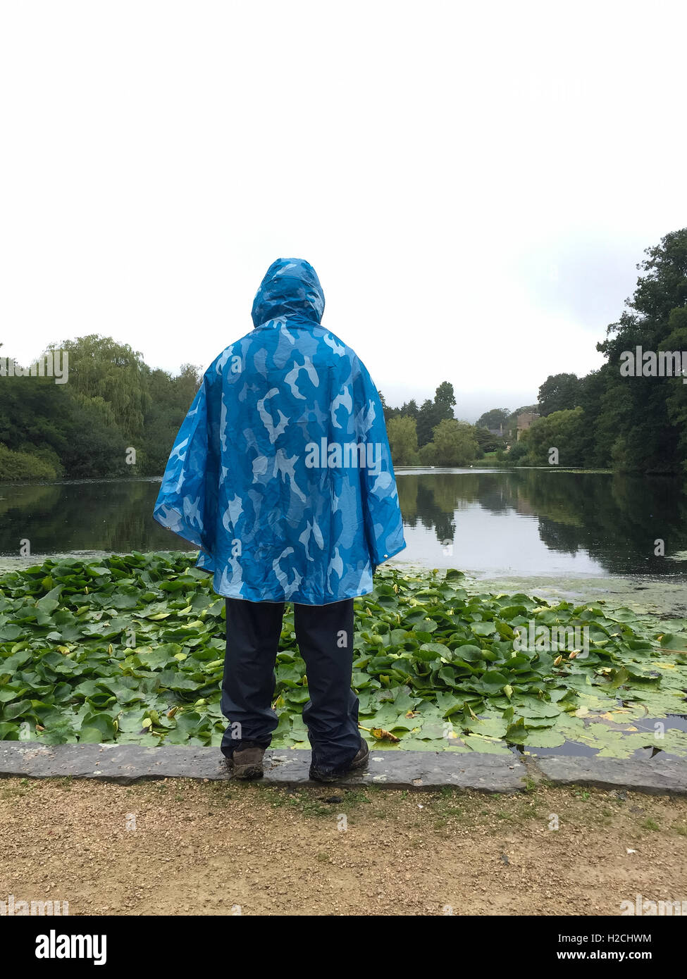 Male hiker wearing waterproof poncho and trousers, at the Garden Lake, Newstead Abbey. - Stock Image