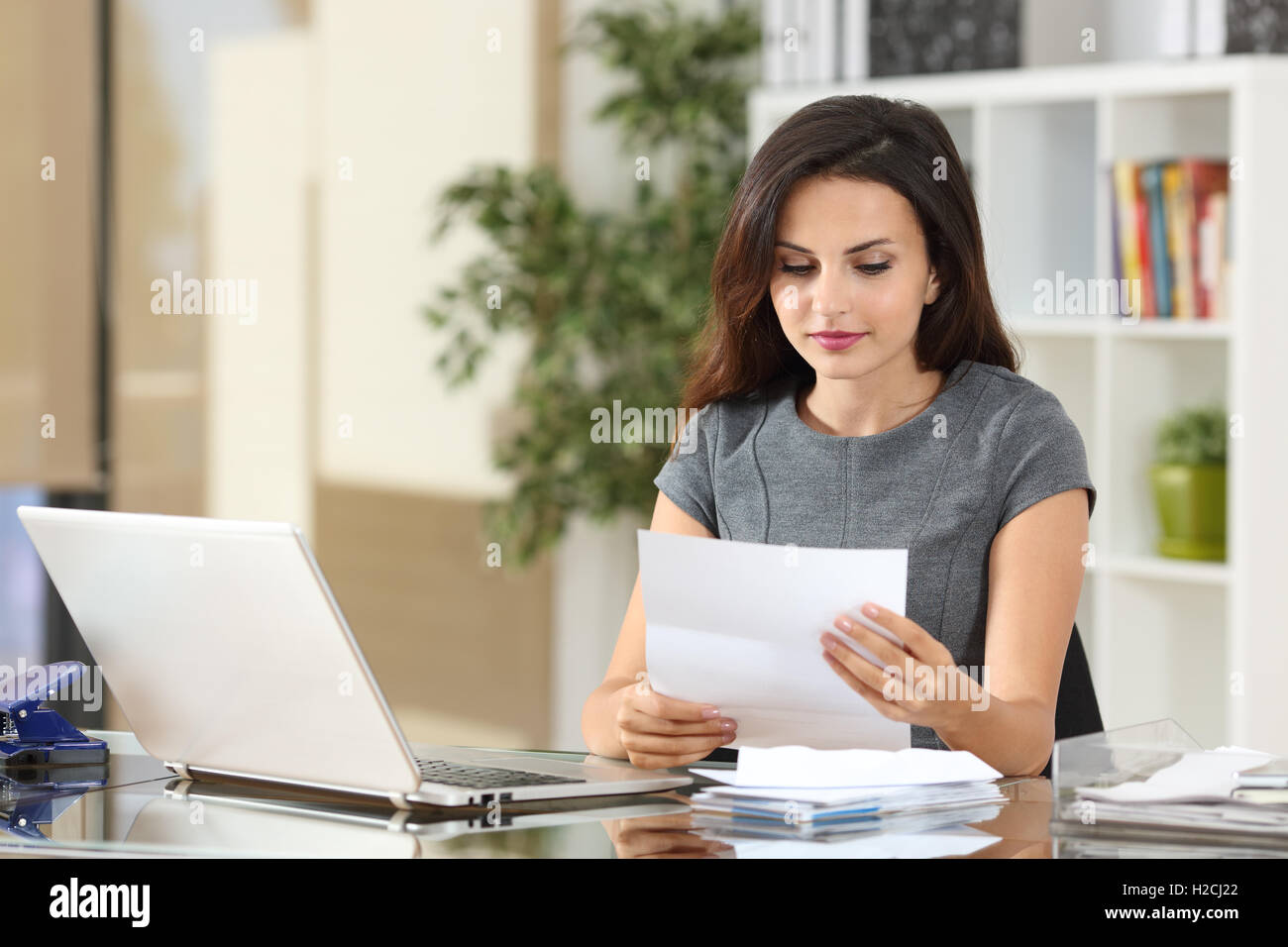Portrait of a businesswoman working at office reading a letter in a desktop - Stock Image
