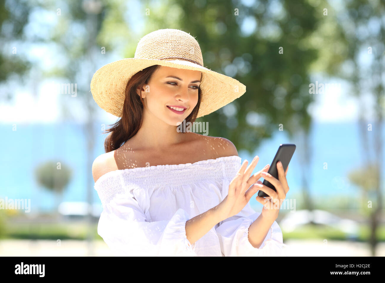 Happy fashion woman wearing picture hat texting on phone in summer with the sea in the background Stock Photo