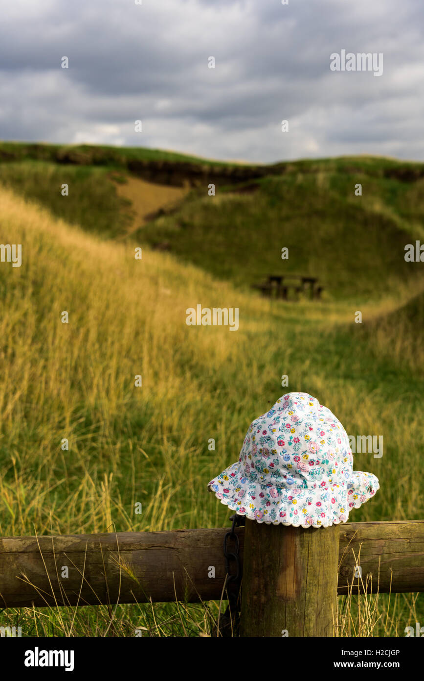 A baby's hat abandoned in British countryside on fence post - Stock Image