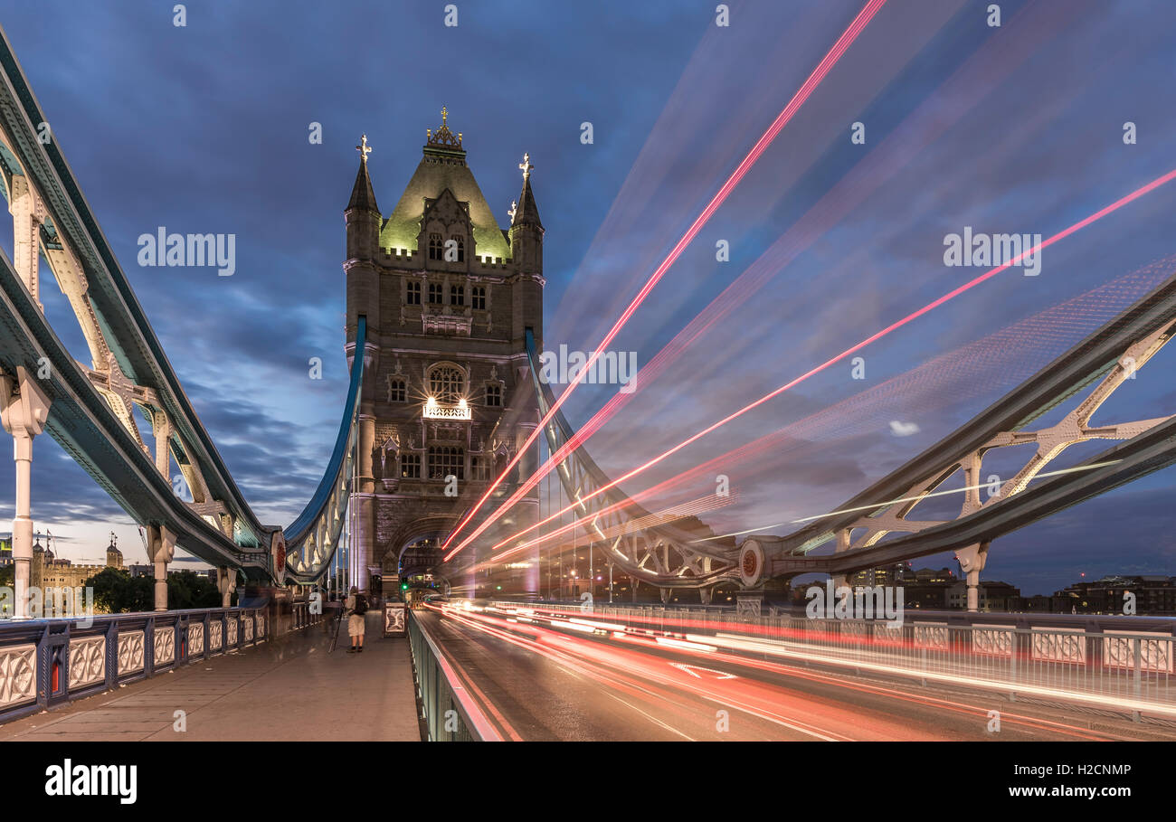 Tower Bridge, London, with traffic light trails passing over the bridge, in the evening - Stock Image
