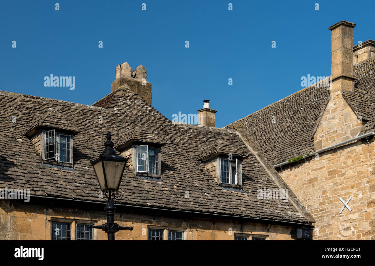 Old Cotswold stone tiled roof with dormer windows, chimneys and old fashioned street lamp - Stock Image