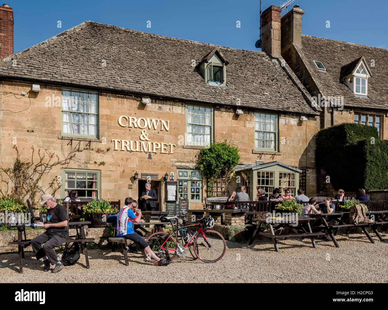 People enjoying an early evening drink in the sunshine in front of a typical village pub in the Cotswolds. - Stock Image