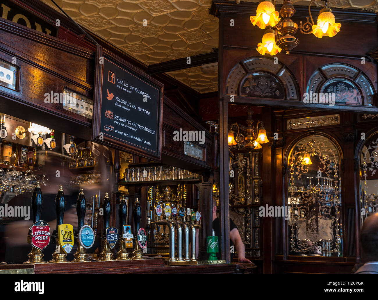 Interior of an old traditional London City Pub with dark wood paneling and cut glass mirrors and row of beer pumps - Stock Image