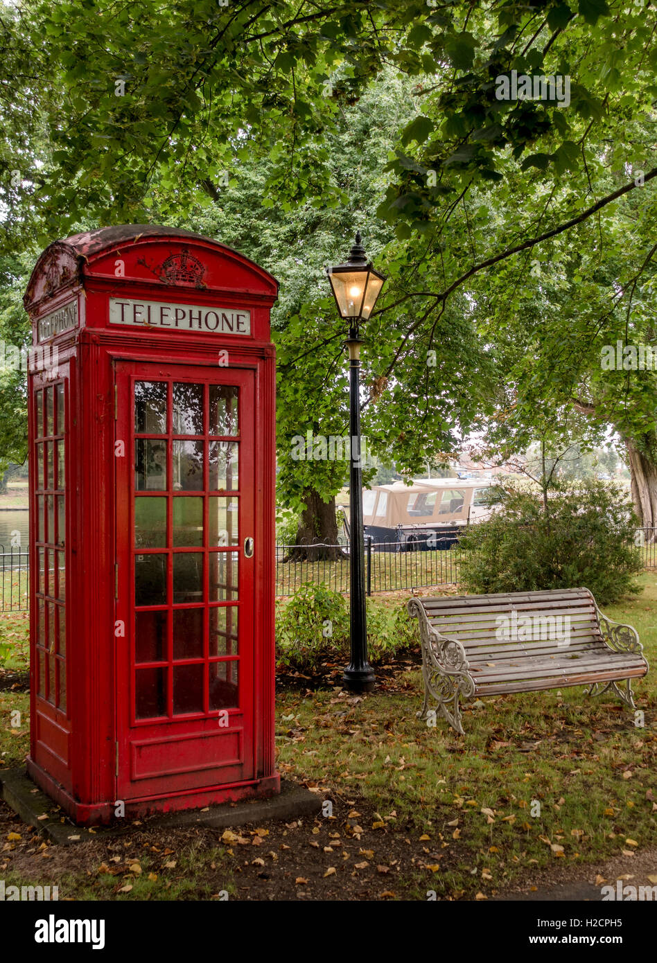 Pre-war 1930's traditional British red telephone box with old lamp post and bench - Stock Image