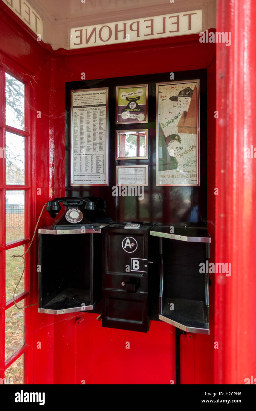 Interior of 1930s traditional British red telephone box showing original phone equipment and posters. - Stock Image
