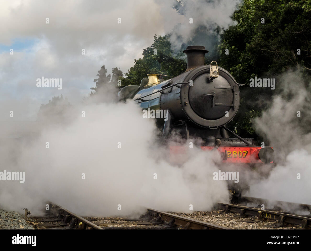 Railway locomotive enveloped in steam at Toddington station - Stock Image