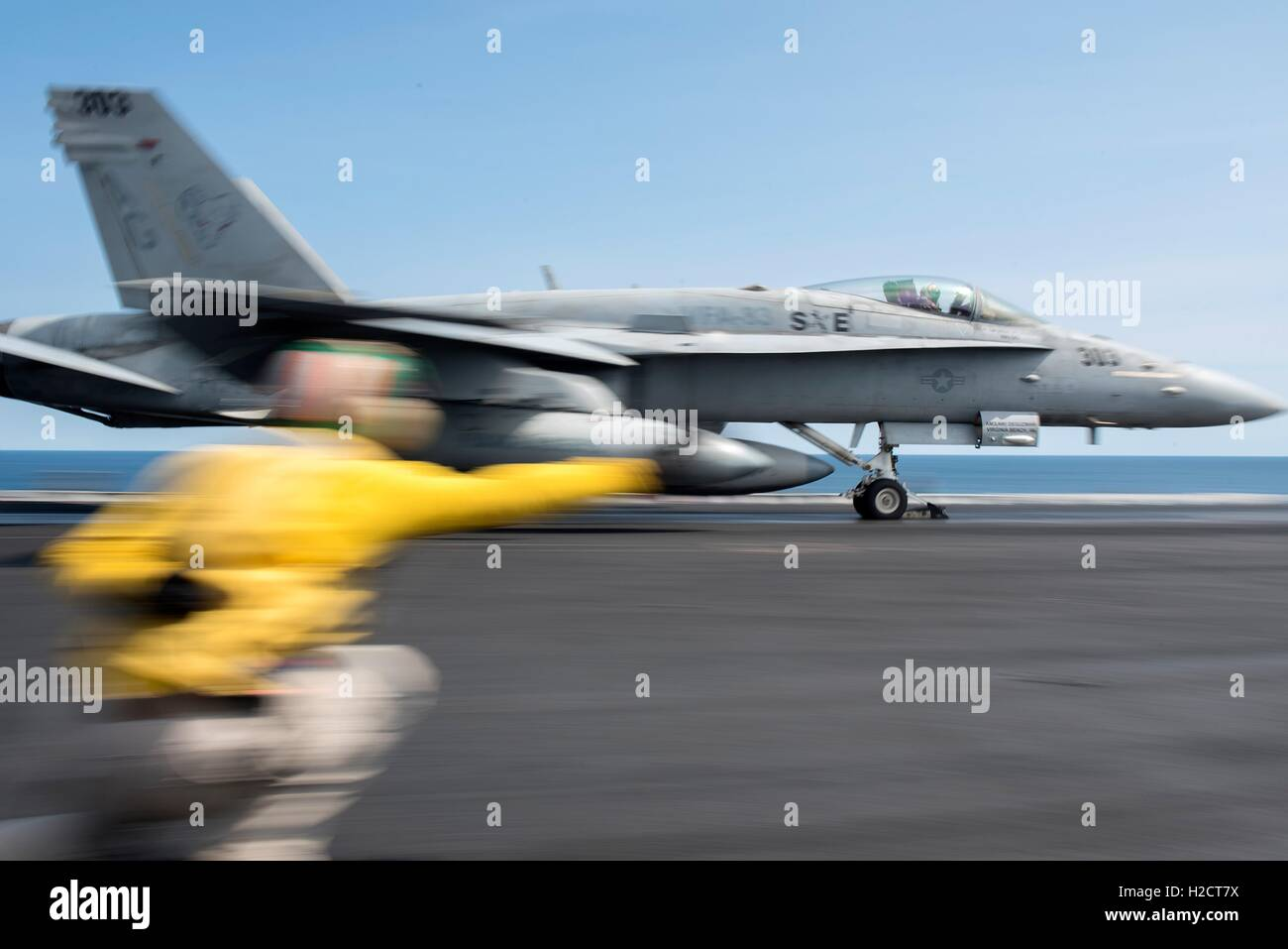 A U.S. Navy flight deck crew officer signals for take-off as a F/A-18C Hornet jet aircraft launches from the flight - Stock Image