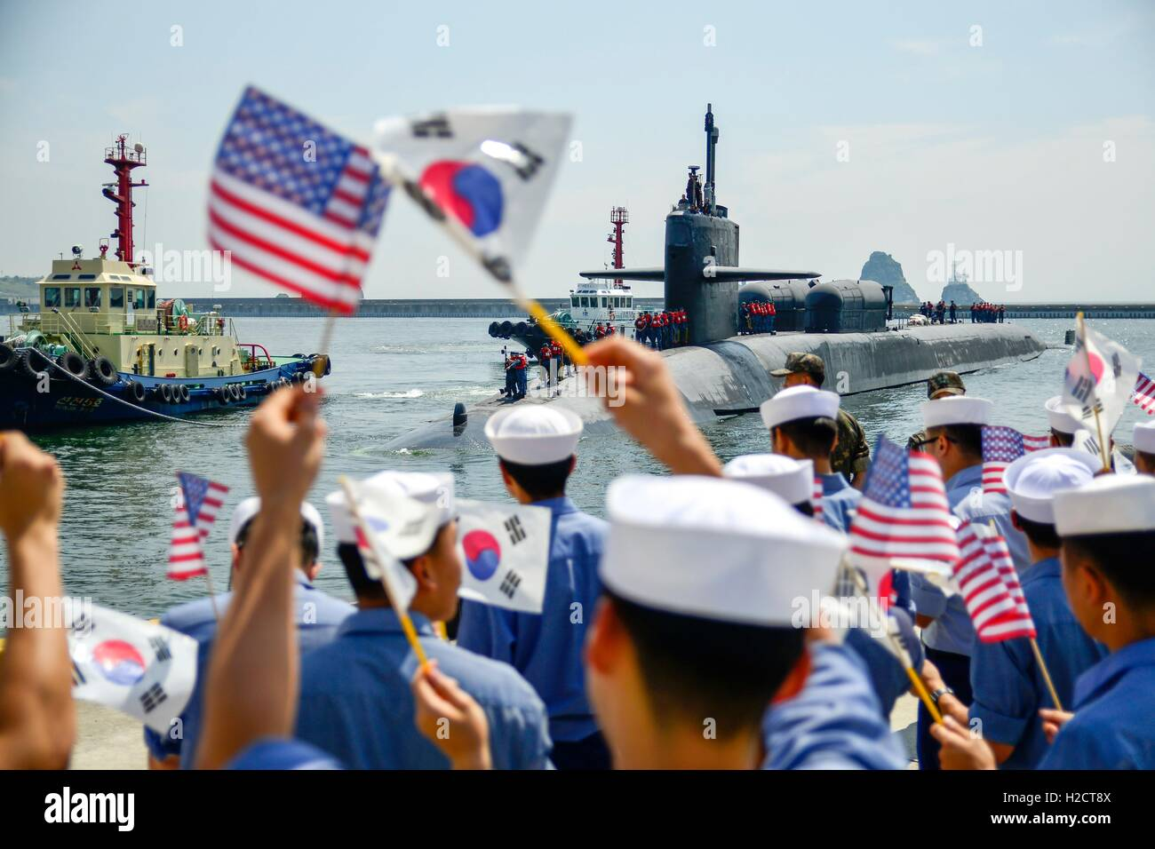 American and Korean sailors wave flags and cheer, welcoming USN Ohio-class nuclear-powered fleet ballistic guided - Stock Image