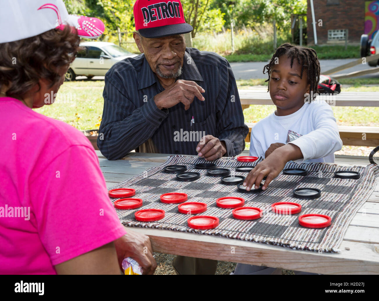 Detroit, Michigan - An elderly man and a young boy team up to play checkers at a block party. Stock Photo