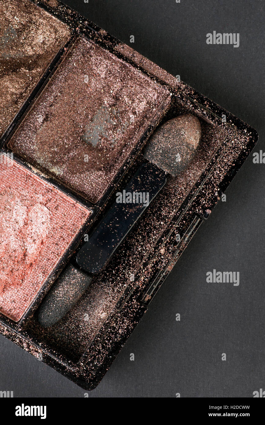 Crushed used eyeshadow in compact box with applicator, covered by eyeshadow dust. On black cardboard background. - Stock Image