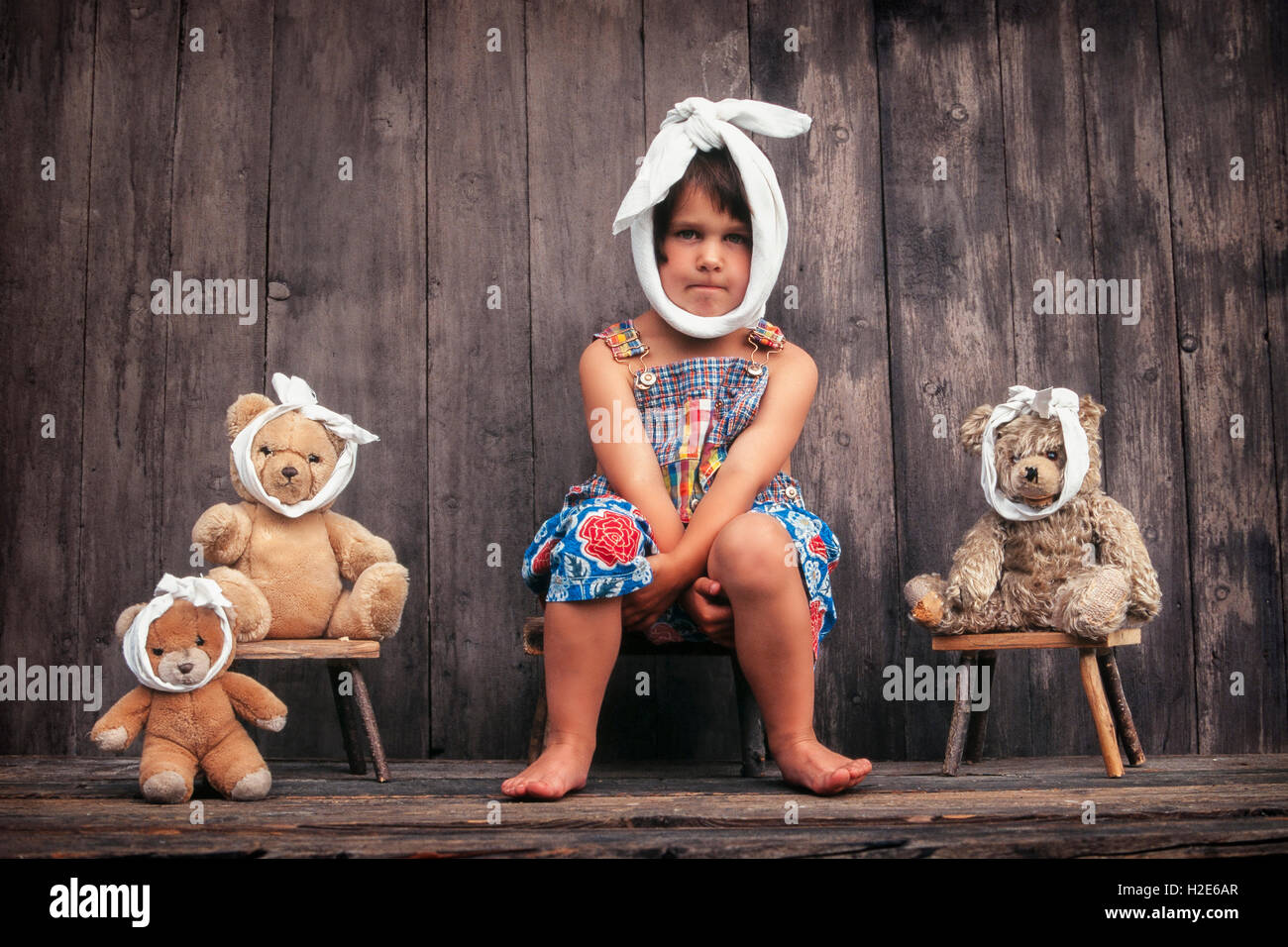 Four-year girl and teddy bears with toothache, sitting in front of wooden hut - Stock Image