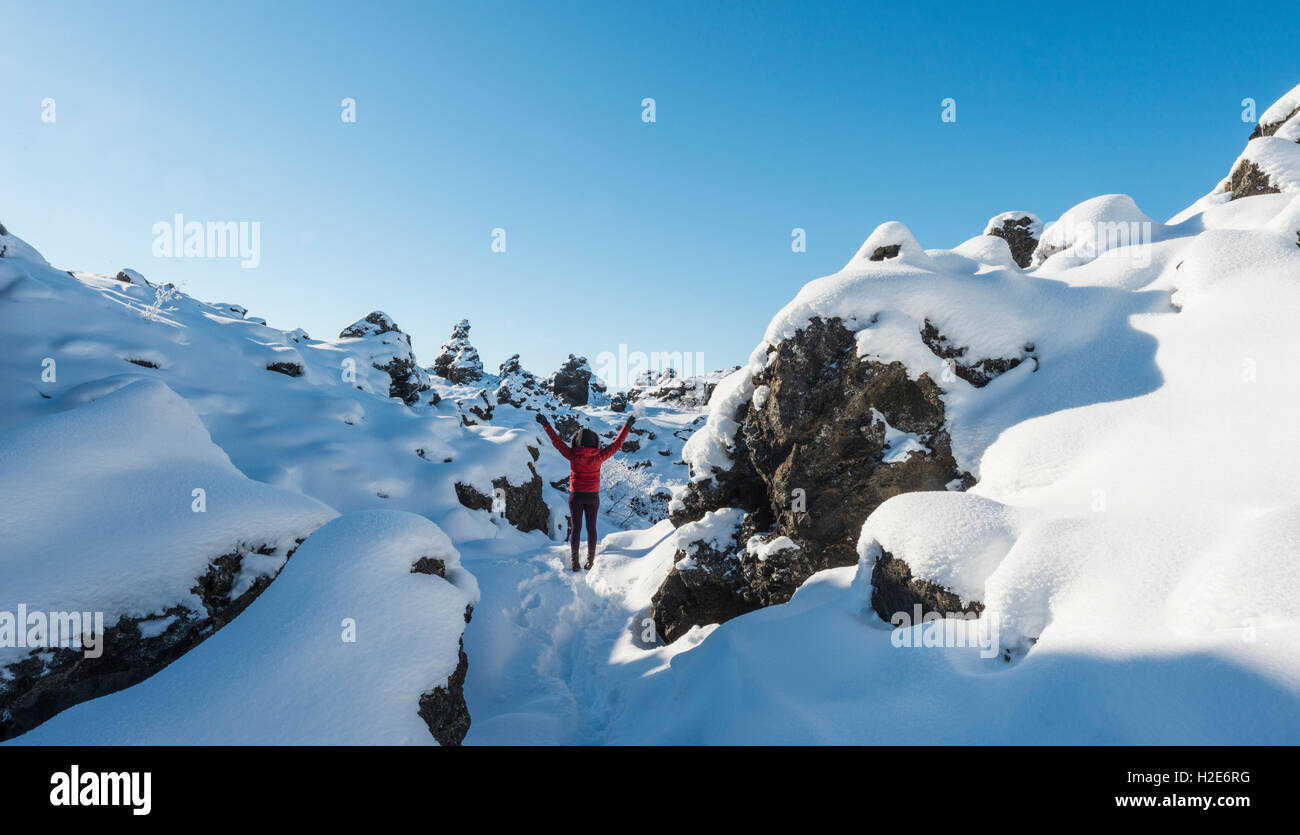 Woman with arms in the air, snowy landscape, lava field covered with snow, Krafla volcanic system, Dimmuborgir National - Stock Image