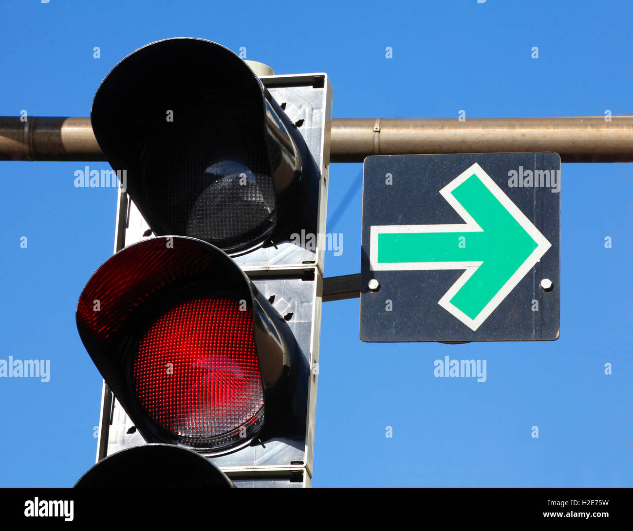Road sign, green arrow and red traffic light, Germany - Stock Image