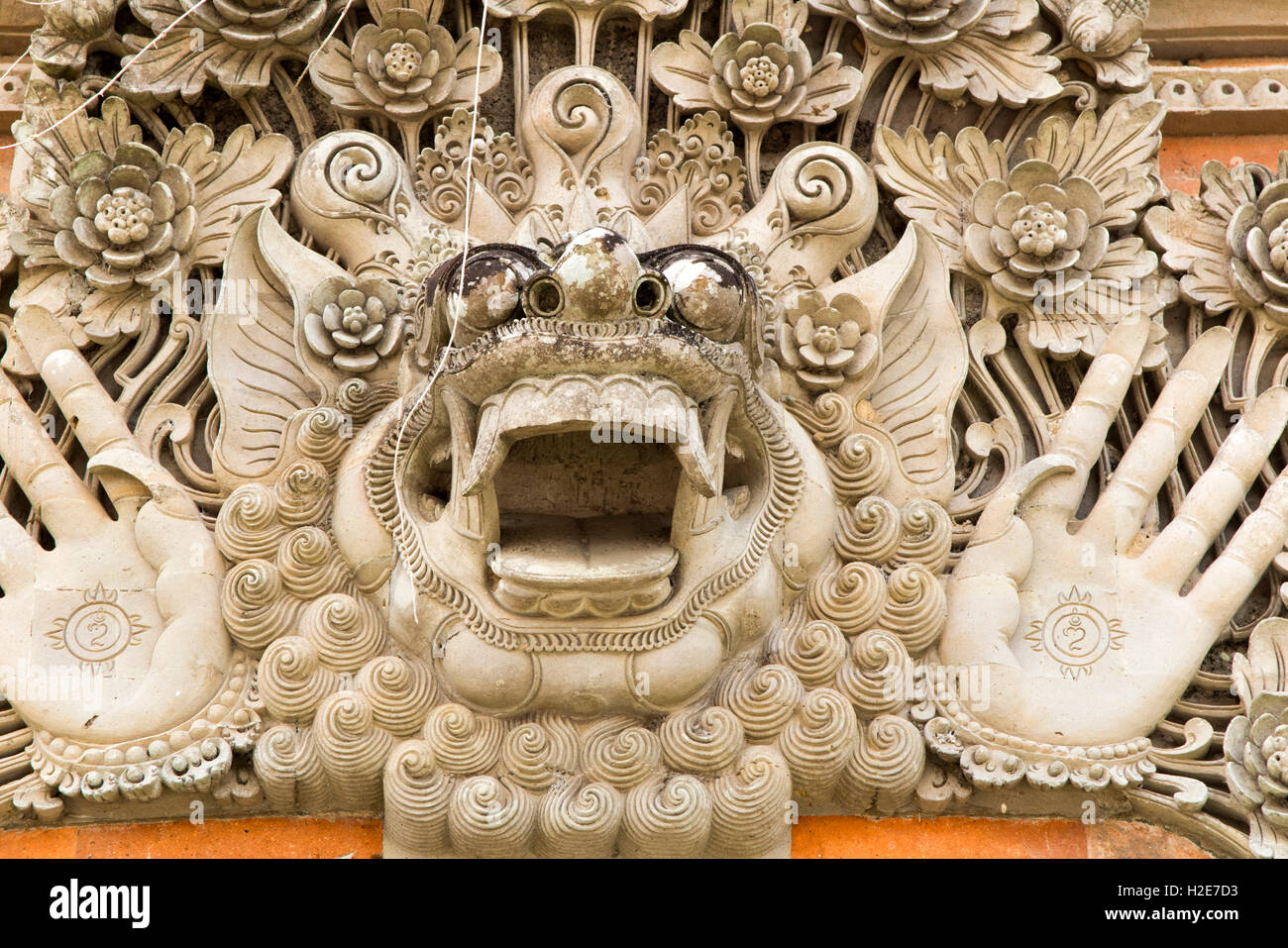 Indonesia, Bali, Payangan, wide mouthed Hindu deity with palms outstretched in local temple - Stock Image