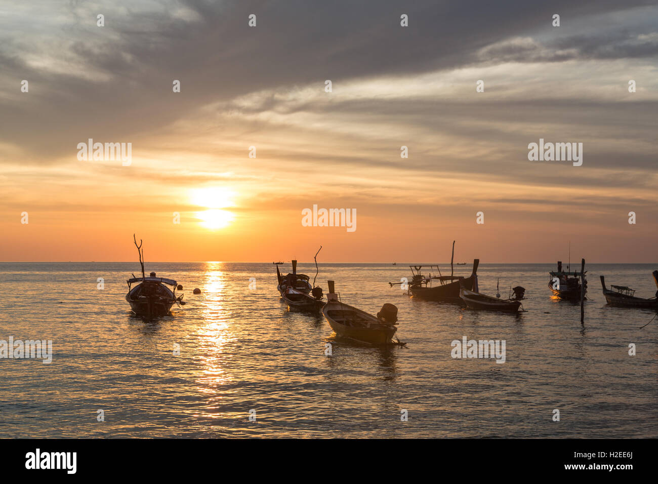 Sunset over long tails boats in Koh Lanta in Krabi province in south Thailand. - Stock Image