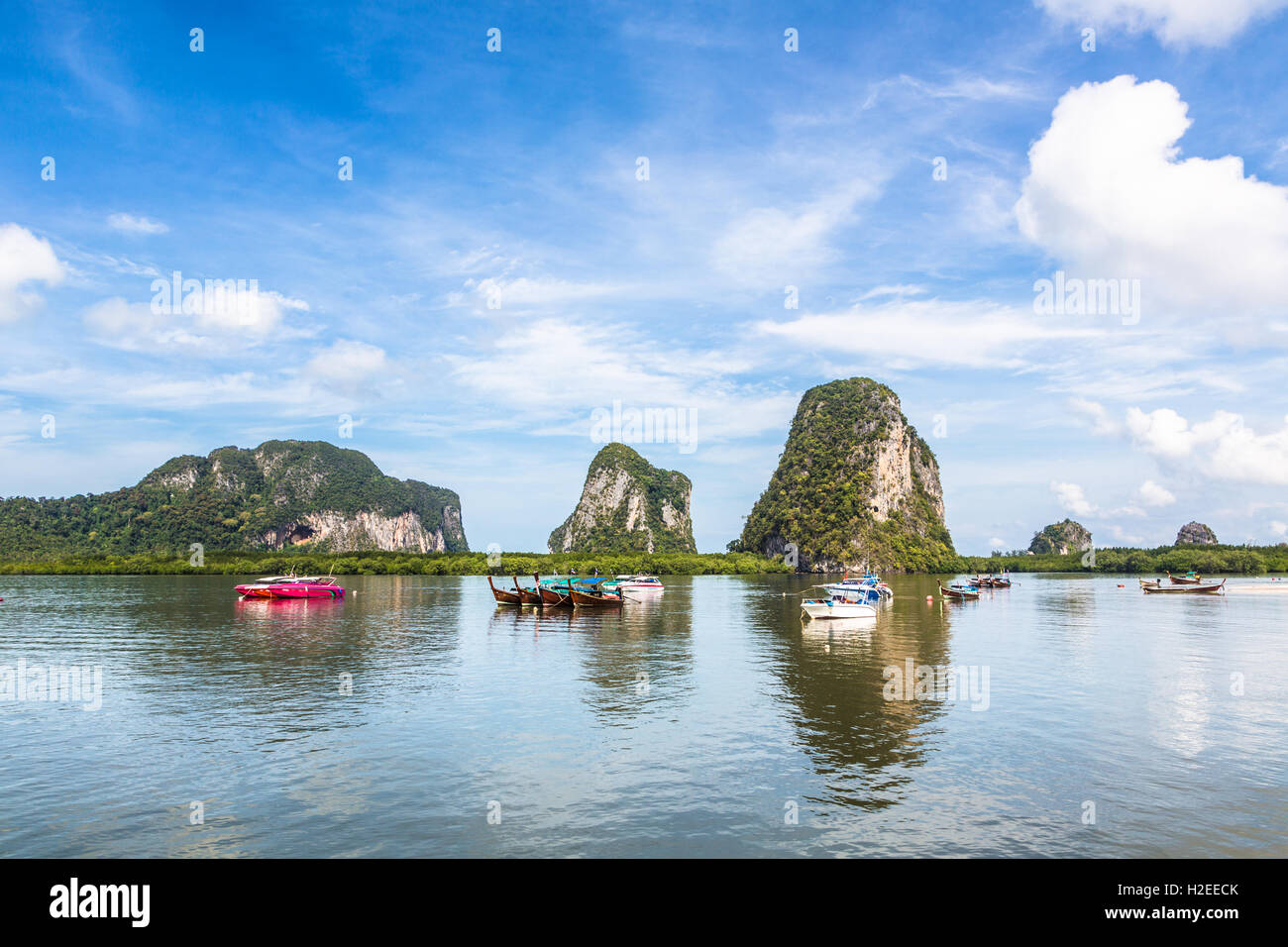 Boats mooring in a bay in front of karst formation in the Trang islands in south Thailand - Stock Image