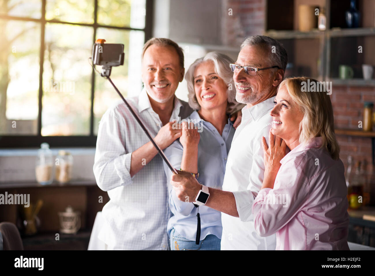 Two elderly couples taking photo in the kitchen - Stock Image