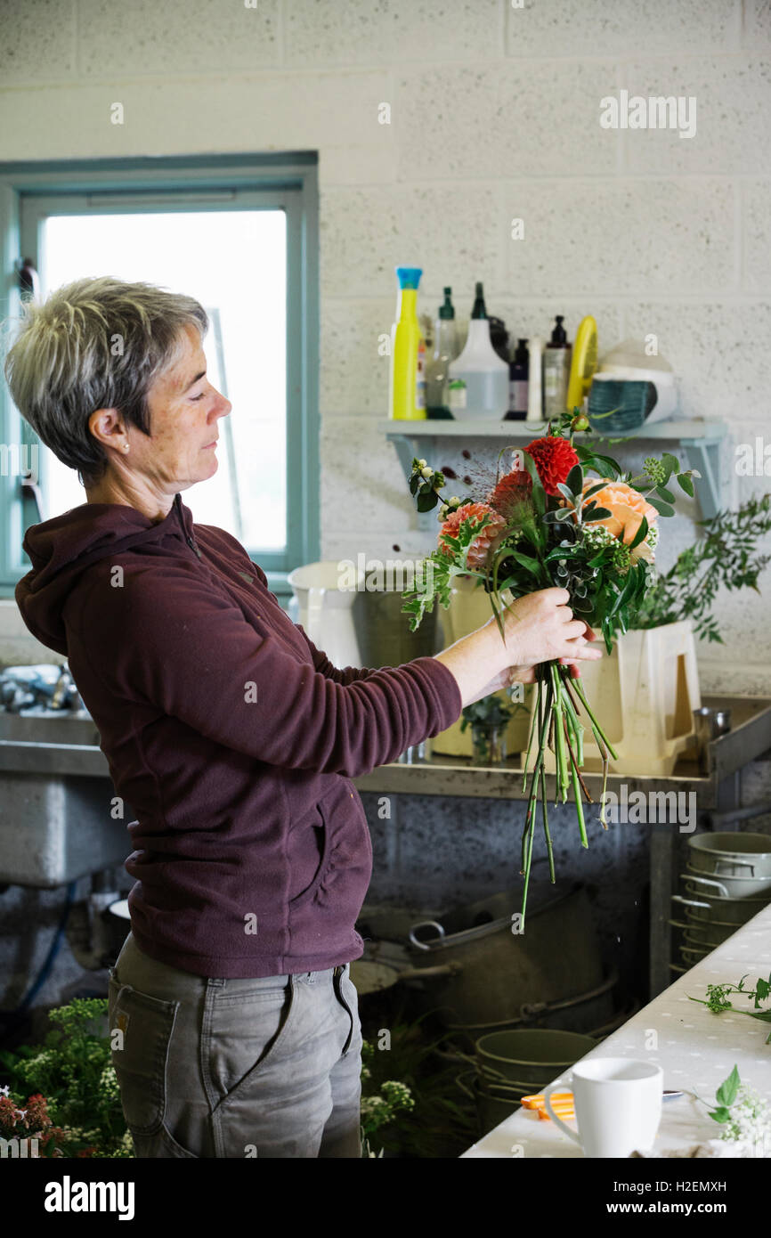 Organic flower arrangements. A woman creating a hand tied bouquet. - Stock Image