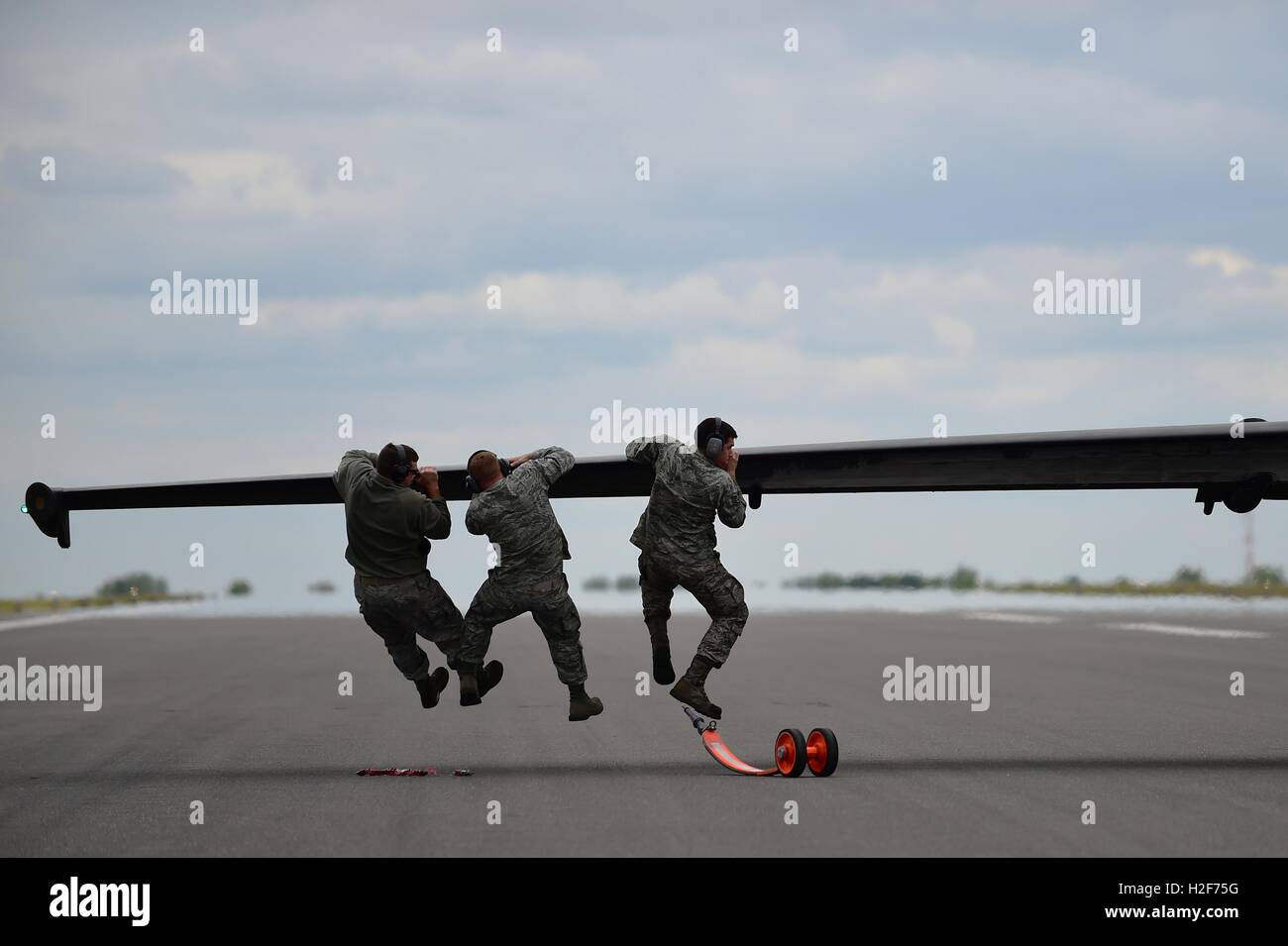 U.S. Air Force soldiers push down on the wing of a U-2 Dragon Lady aircraft after landing at Royal Air Force Fairford - Stock Image