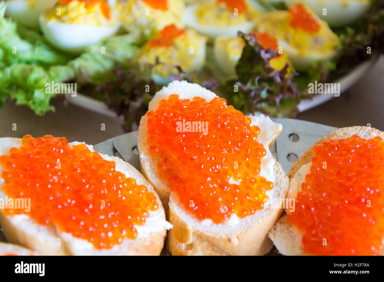 Sandwiches with red caviar on a celebratory table - Stock Image